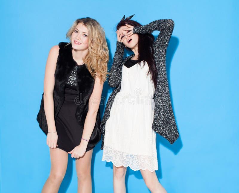 Modieuze mooie jonge meisjes die zich dichtbij een blauwe achtergrond verenigen Het hebben van grappig en het stellen het bekijke stock foto's