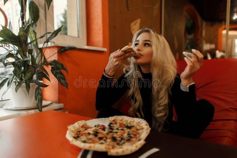 Modieuze mooie jonge vrouw die pizza eten bij een lijst in een koffie stock afbeelding