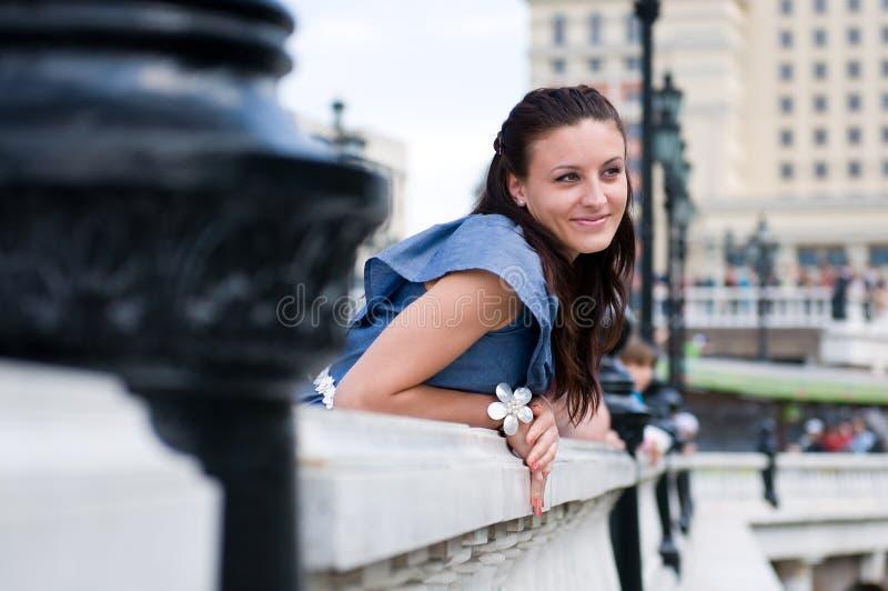 Modieuze mooie jonge vrouw in het mooie kleding stellen op balkon stock foto