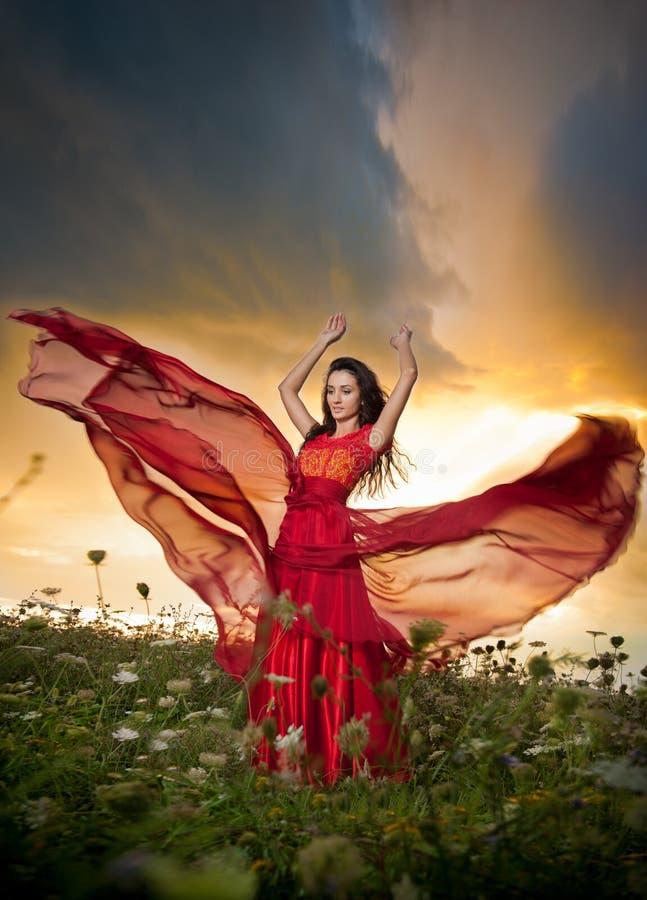 Modieuze mooie jonge vrouw in het lange rode kleding stellen openlucht met bewolkte dramatische hemel op achtergrond Aantrekkelij royalty-vrije stock afbeeldingen