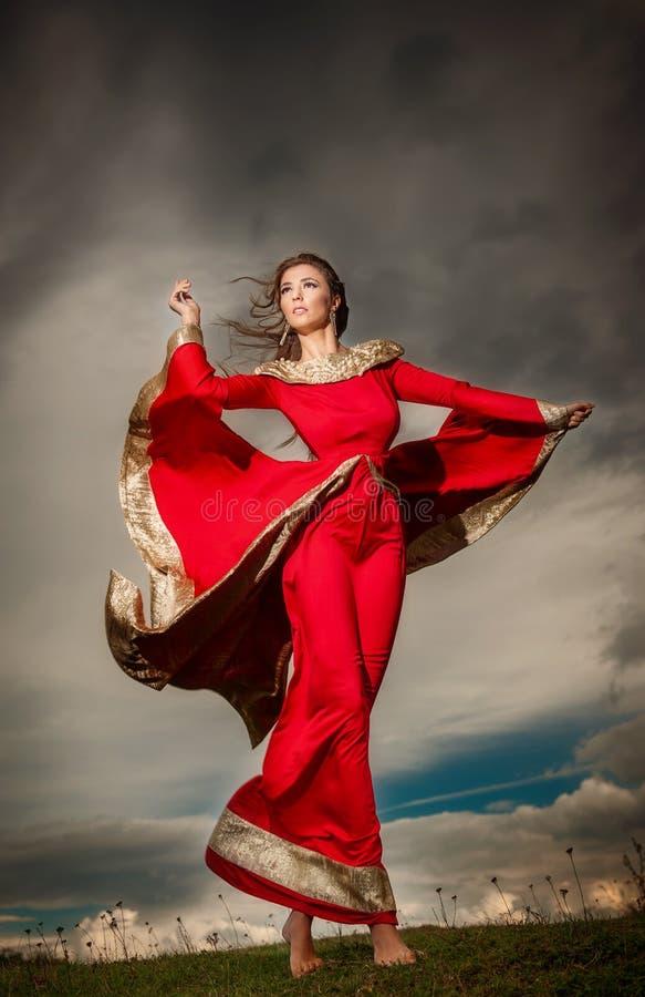 Modieuze mooie jonge vrouw in het rode lange kleding stellen openlucht met bewolkte dramatische hemel op achtergrond stock fotografie