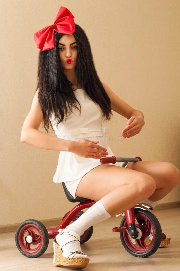Modieuze mooie vrouw in het beeld van pop op fiets royalty-vrije stock afbeelding
