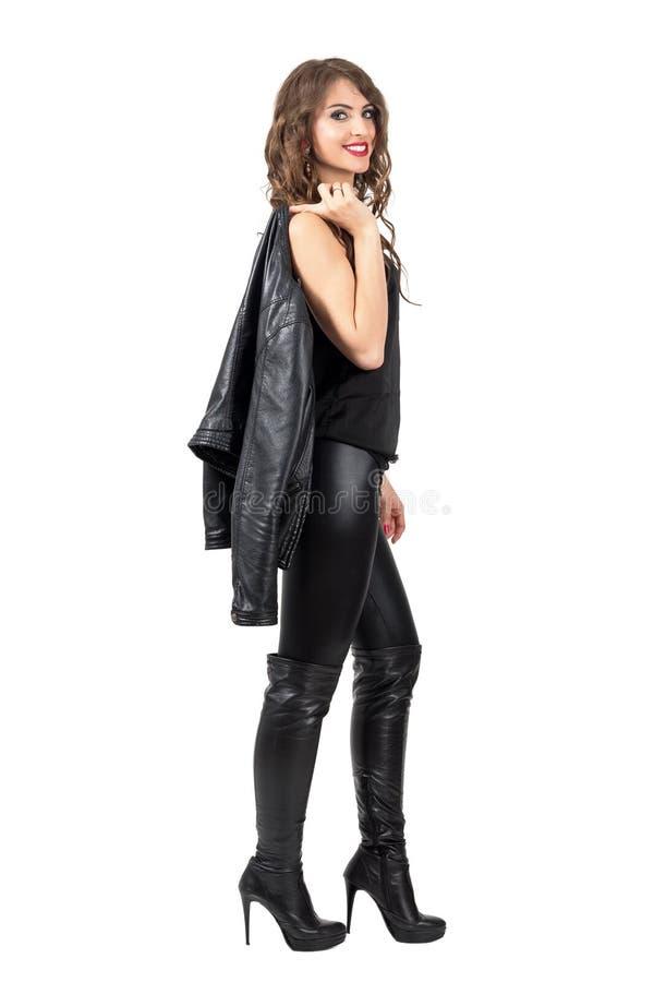 Modieuze mooie vrouw in leerlaarzen en broek die leerjasje over haar schouder dragen stock afbeelding