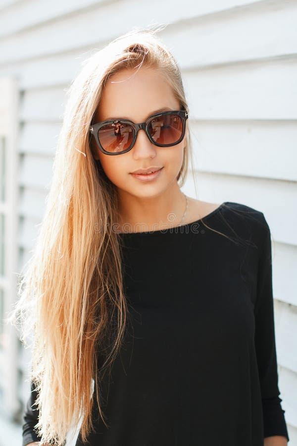 Modieuze mooie vrouw in zonnebril dichtbij een houten muur royalty-vrije stock afbeelding