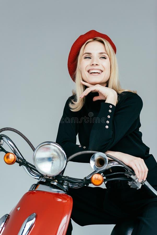Modieuze mooie vrouw in zwarte kleren die door rode motorfiets stellen royalty-vrije stock fotografie