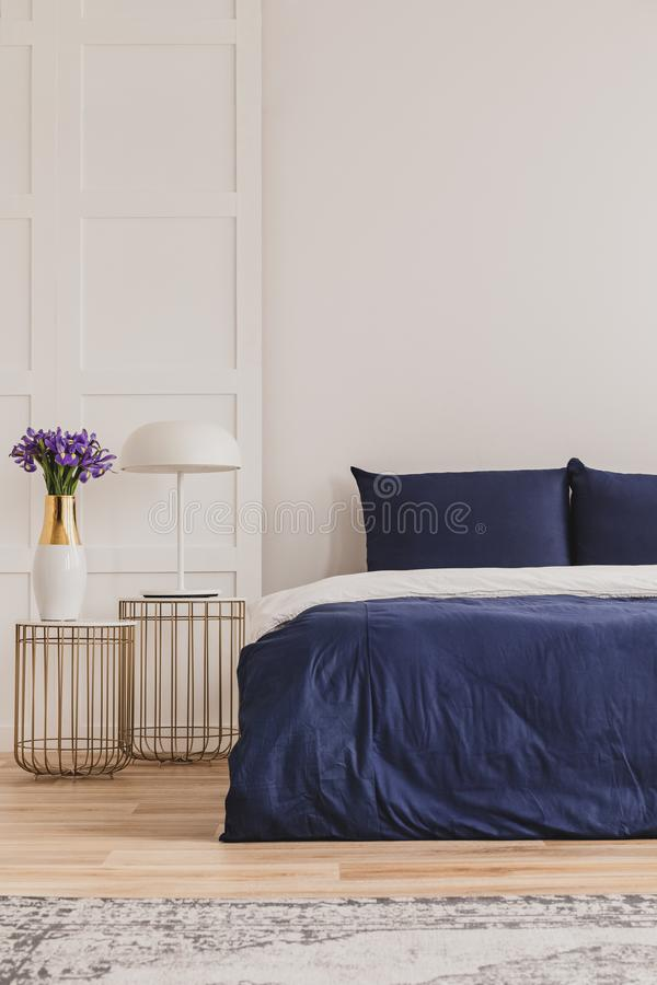 Modieuze nightstand met industriële lamp en in bedlijst met bloemen in vaas naast eenvoudig marineblauw bed stock fotografie