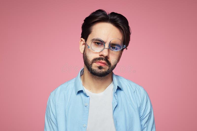 Modieuze ongeschoren kerel met bored gevoede die omhoog uitdrukking, na een lange harde die werkdag wordt vermoeid, over roze ach stock foto