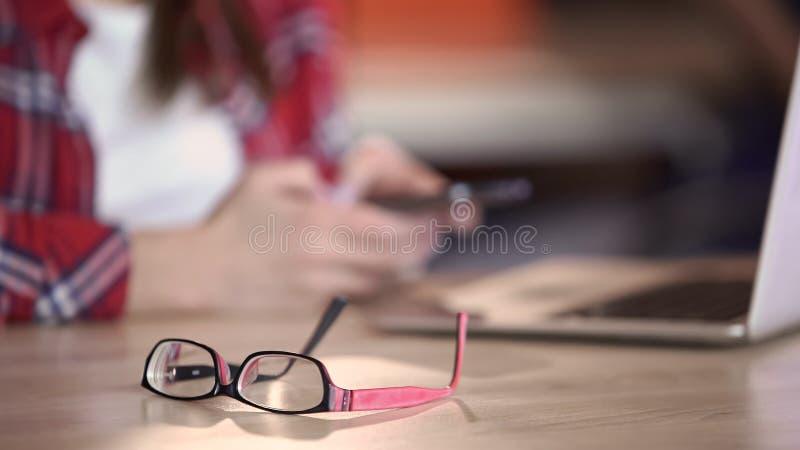 Modieuze oogglazen die op lijst, vrouw het texting aangaande smartphone, mededeling liggen stock afbeeldingen