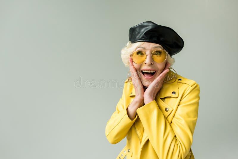 modieuze opgewekte hogere vrouw in gele jasje en leerbaret, stock afbeeldingen