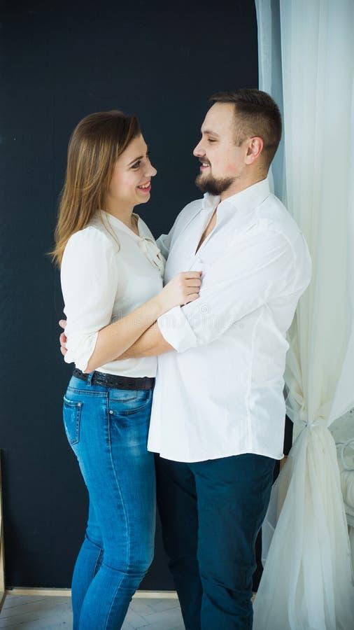 Modieuze paar-mens en vrouw in het witte overhemden en jeans koesteren foto in heldere kleuren stock foto