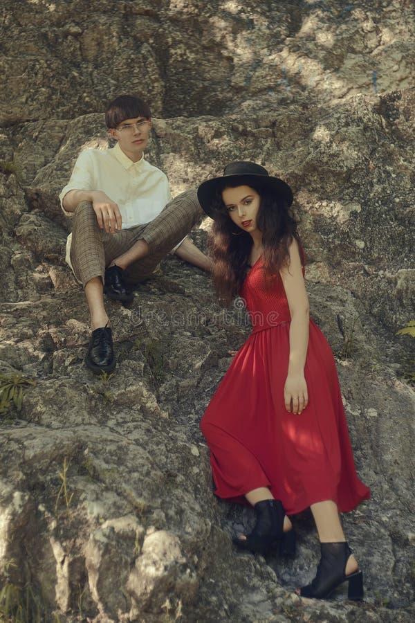 Modieuze paarzitting op de rotsen Hipstervrouw met een modieuze rode lange kleding Man en vrouw in de bergen royalty-vrije stock afbeeldingen