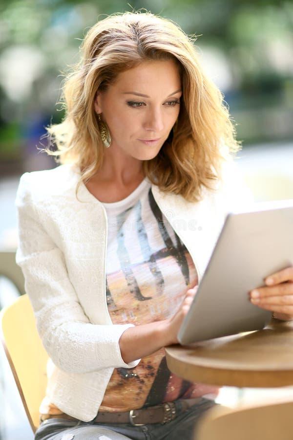 Modieuze rijpe die vrouw op tablet wordt verbonden stock afbeeldingen