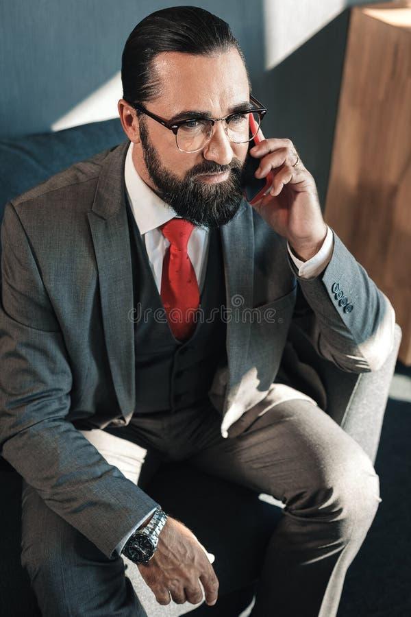 Modieuze rijpe zakenman die rode band dragen die zijn partner roepen royalty-vrije stock foto's