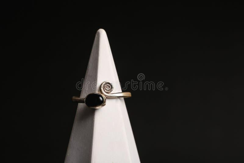 Modieuze ring op tribune tegen zwarte achtergrond Luxejuwelen royalty-vrije stock afbeeldingen