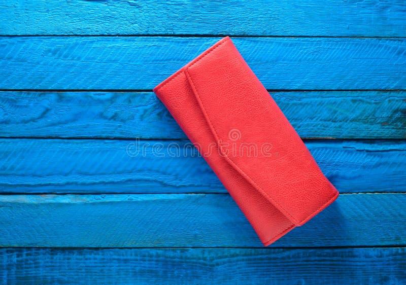 Modieuze rode beurs op een blauwe houten achtergrond Hoogste mening Tendens van minimalism stock fotografie