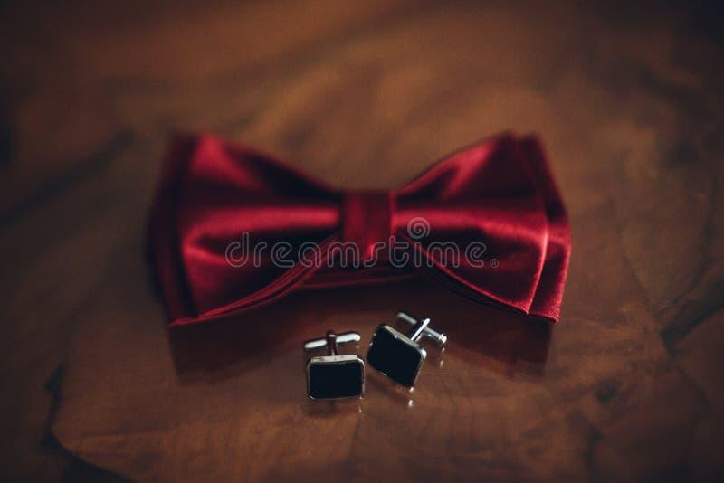 Modieuze rode vlinderdas en manchetknopen op houten lijst, bruidegom het krijgen stock foto's