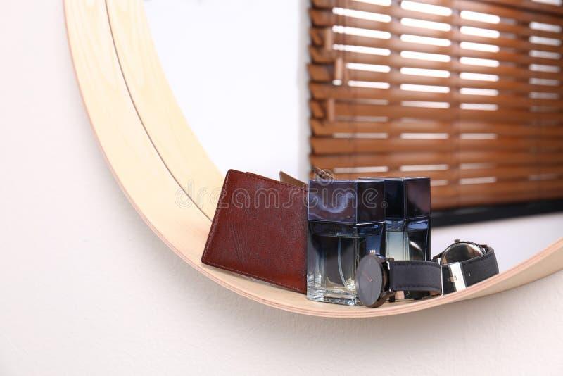 Modieuze ronde spiegel met mannelijke toebehoren op witte muur binnen Binnenlands stock foto's