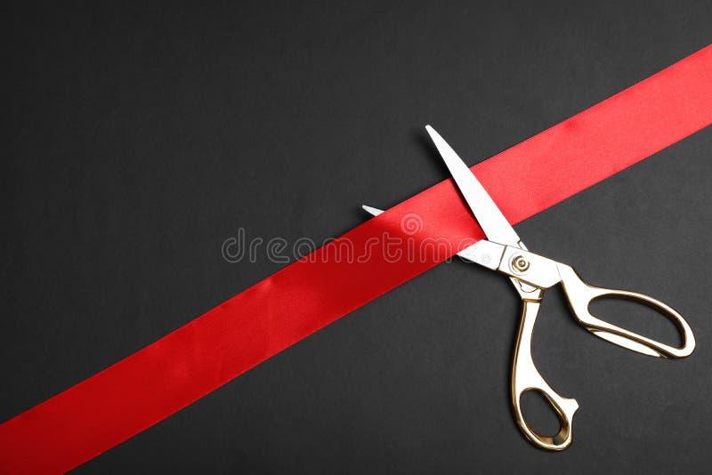 Modieuze schaar en rood lint op zwarte achtergrond, ruimte voor tekst Plechtig bandknipsel stock afbeelding