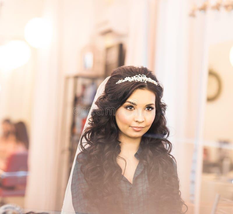 Modieuze schitterende bruid die make-up in de zaal van de luxeschoonheid met grote spiegels en licht krijgen royalty-vrije stock foto