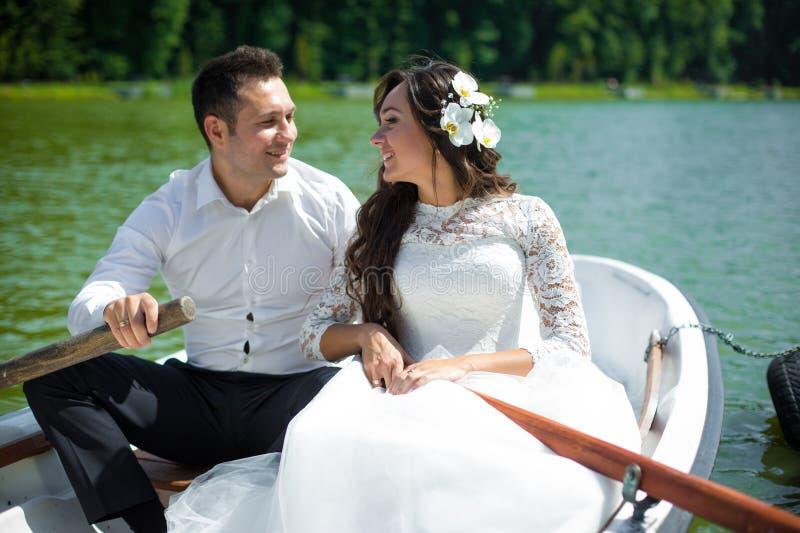 Modieuze schitterende gelukkige donkerbruine bruid en elegante bruidegom in B stock foto's