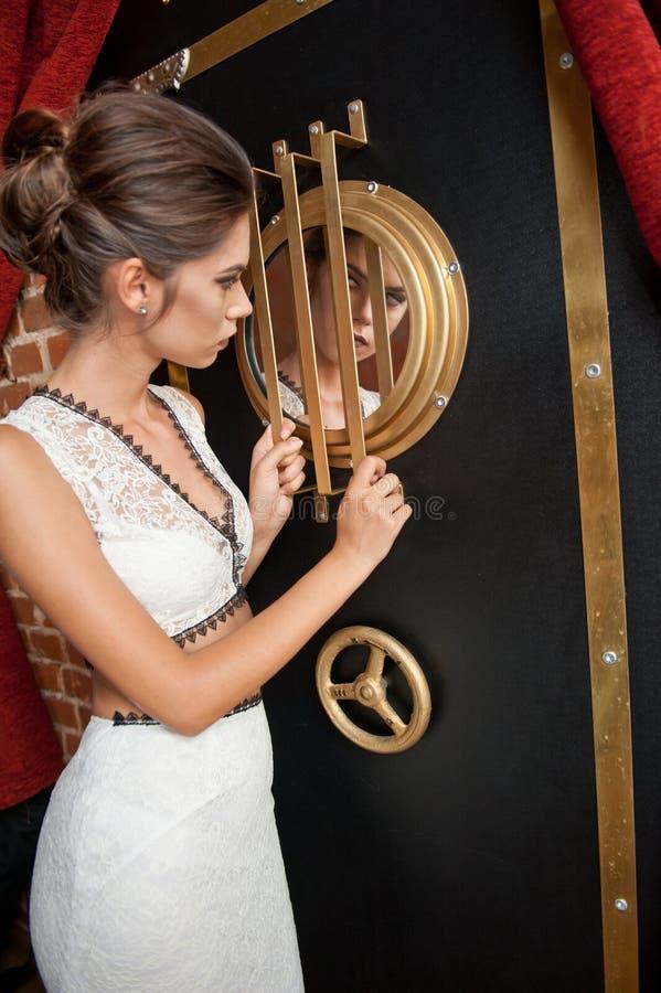 Modieuze sensuele aantrekkelijke dame met witte kleding die zich dichtbij een brandkast in een uitstekende scène bevinden Korte h royalty-vrije stock foto