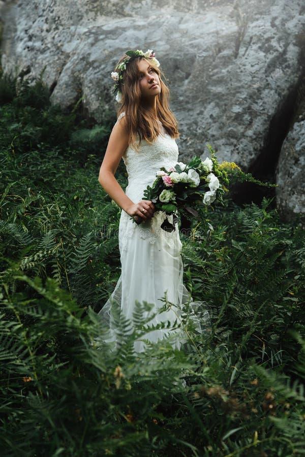 Modieuze sensuele Boheemse bruid in een fairytale met boeket op achtergrond van rotsen in bergen royalty-vrije stock foto's