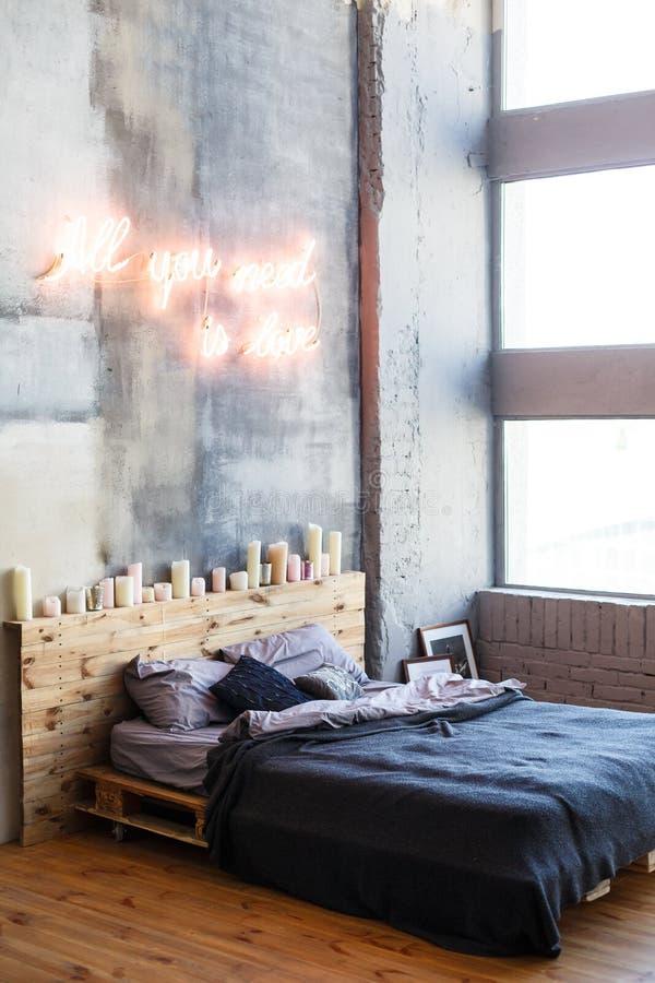 Modieuze slaapkamer in zolderstijl met grijze kleuren en vele kaarsen royalty-vrije stock foto