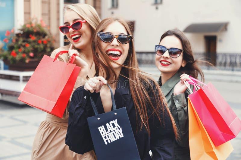 Modieuze Slanke Dames die met Kleurrijke het Winkelen Zakken lopen stock afbeelding