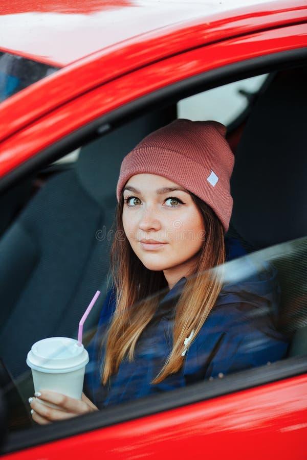 Modieuze sportieve donkerbruine vrouw in in stedelijke outwear drijvend een auto met de grote witte beschikbare Wijnoogst van de  stock foto