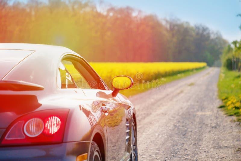 Modieuze sportwagen op een landelijke weg Mooi landschap, zonnige dag stock afbeelding