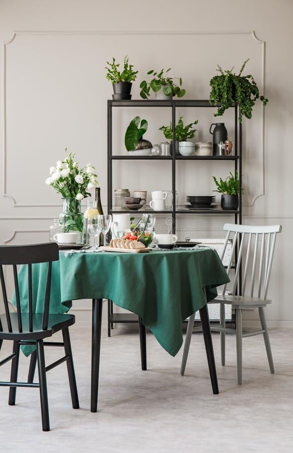 Modieuze stoelen bij rondetafel met groen tafelkleed in grijze eetkamer stock foto