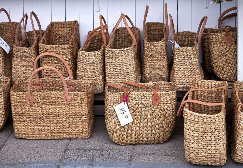 Modieuze stro het winkelen zakken bij markt stock fotografie