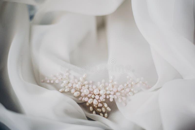 Modieuze tedere parelhaarspeld op zacht wit Tulle in ochtendlicht in hotelruimte Bruids toebehoren voor de huwelijksdag modern royalty-vrije stock afbeelding