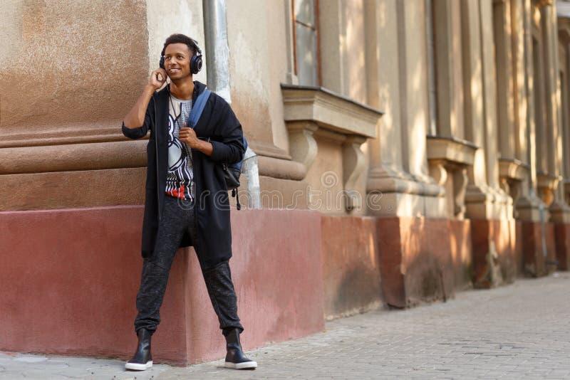 Modieuze toevallige multi gerende jonge mens die een muziek die buiten luisteren, zich dichtbij muur, in straat met exemplaarruim royalty-vrije stock foto