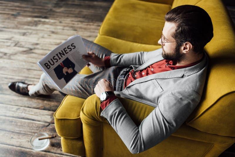 modieuze van de bedrijfs mensenlezing krant en zitting stock afbeeldingen