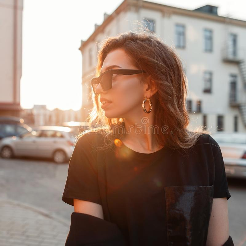 Modieuze vrij aantrekkelijke jonge hipstervrouw in in donkere zonnebril in het modieuze zwarte T-shirt stellen in de stad bij zon stock foto
