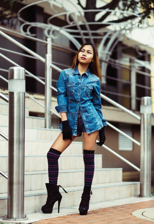 Modieuze vrij jonge vrouw jeans dragen, en lange gestreepte kniesokken die stock fotografie