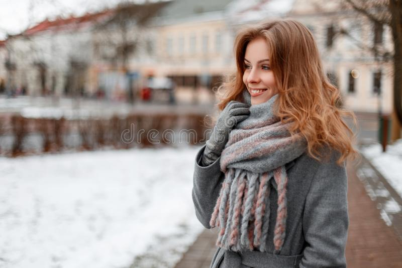 Modieuze vrij jonge vrouw met een mooie glimlach in een grijze elegante laag in een modieuze grijze sjaal in handschoenen die ron stock foto's