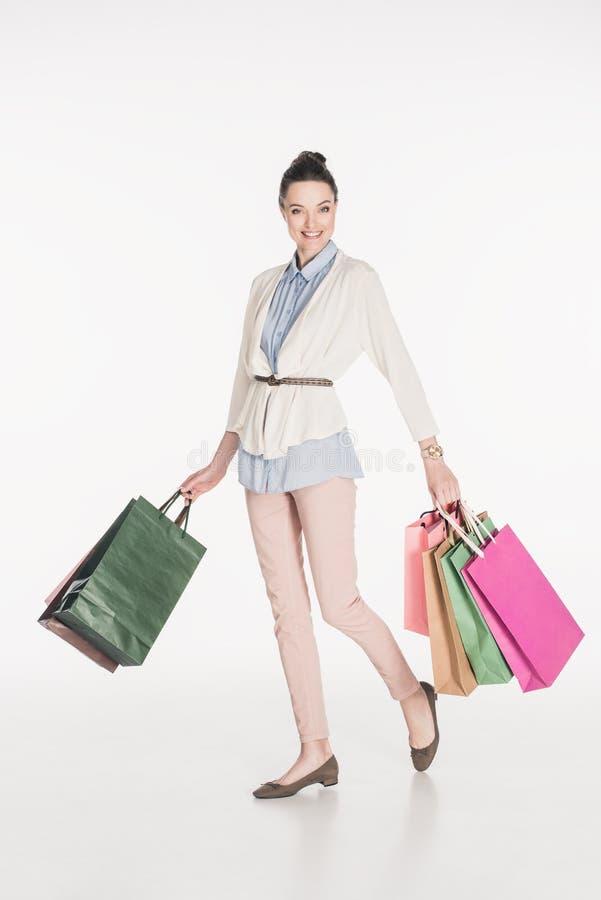modieuze vrolijke vrouw met het winkelen zakken in handen stock foto