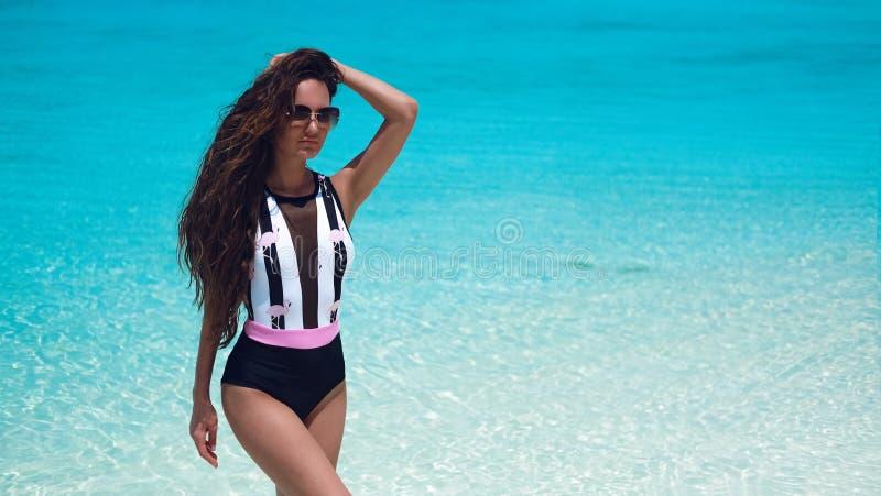 Modieuze Vrouw in bikini het suntanning op tropisch strand Vrij het slanke meisje stellen op exotisch eiland door mooie turkooise royalty-vrije stock foto's