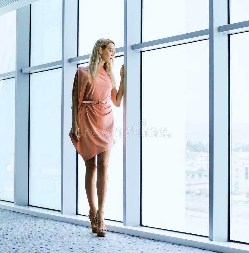 modieuze vrouw dichtbij het venster in het bureaugebouw stock fotografie