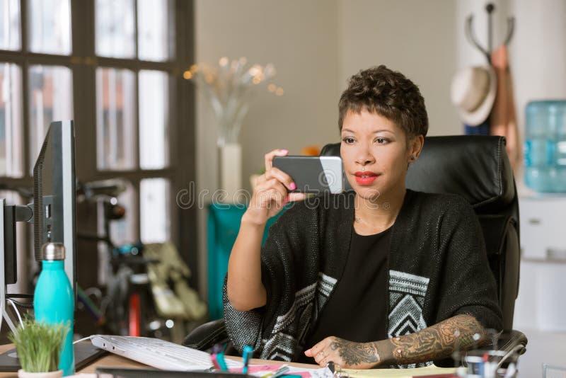 Modieuze Vrouw die een Telefoon in Haar Bureau met behulp van royalty-vrije stock afbeelding