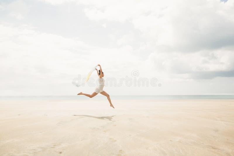 Modieuze vrouw die met sjaal springen stock fotografie