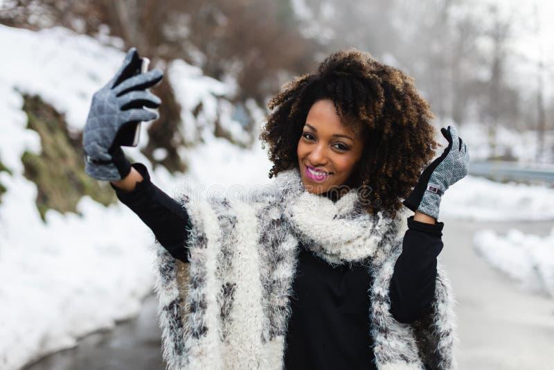 Modieuze vrouw die selfie met smartphone in de winter nemen royalty-vrije stock fotografie