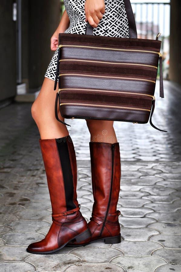 Modieuze vrouw die in stadsstraat lopen, bruine leerlaarzen dragen en bruine leer en suèdezak houden royalty-vrije stock foto's