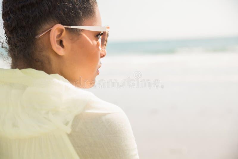 Modieuze vrouw die uit aan overzees kijken stock foto