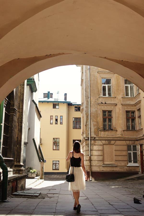 Modieuze vrouw die zich in zonlicht onder boog van oud bouwturkije bevinden stock foto