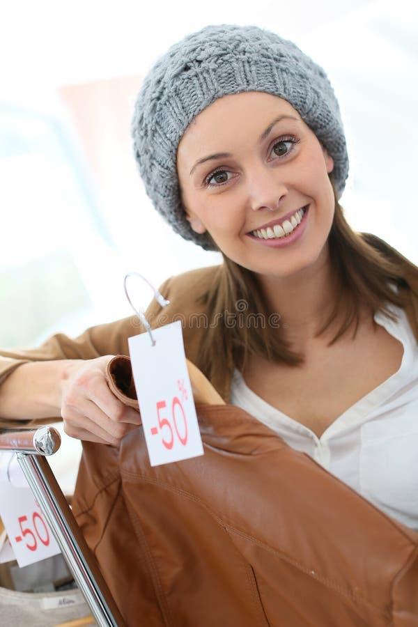 Modieuze vrouw in een kledingsopslag stock afbeelding