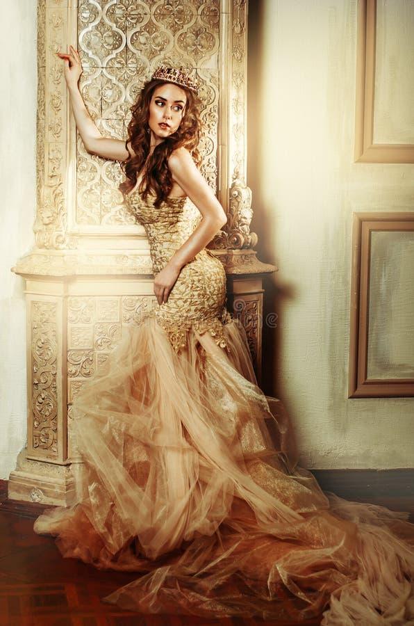 Modieuze vrouw in een lange gouden kleding in mooi binnenland royalty-vrije stock fotografie