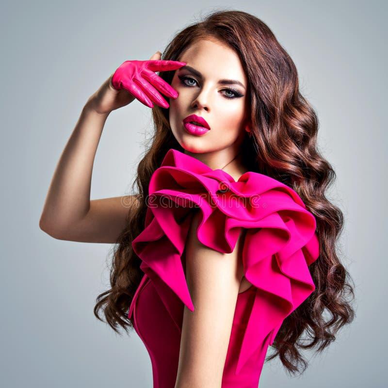 Modieuze vrouw in een rode kleding met een creatieve oogmake-up stock afbeelding